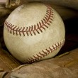 Worn leather baseball glove holding a baseball — Stock Photo #19748333