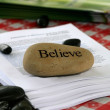 Believe stone used as paper weight - Stock Photo