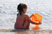 Small girl playing at a beach with a plastic bucket — Stock Photo