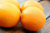 Macro shot of fresh oranges on a wooden table — Stock Photo