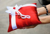 Woman hold a red pillow with golden wedding rings — Stock Photo