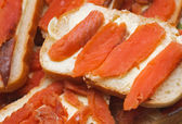 Salted red pieces of fish on a bread. delicacy food — Stock Photo