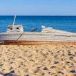 Old wooden fishing boat  lying on a seashore — Stok fotoğraf
