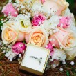 Wedding bouquet and pair rings lying of forest coniferous ground - Stock Photo