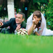 Groom and bride lie on a grass around soap bubbles — Stock Photo #27558257