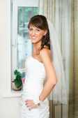 Beautiful happy bride in a white dress looking at camera — Stock Photo
