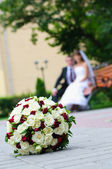 Elegant wedding bouquet with many roses on blur newlywed backgro — Stock Photo