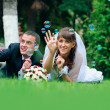 Groom and bride lie on a grass around soap bubbles — Stock Photo #28309971