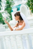 Pensive bride in a white dress looks at manicure — Stock Photo