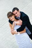 Happy wedding couple standing and embracing — Stock Photo