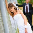 Beauty bride in white dress standing near fence. Groom behind — Stock Photo