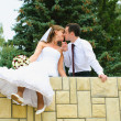 Stock Photo: Wedding couple kiss and dangle feet. Tenderness loving