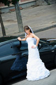 Happy bride in white dress standing near wedding car — Stock Photo
