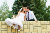 Wedding couple kiss and dangle feet. Tenderness loving — Stock Photo