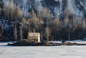 Frozen lake with one house in a mountain land — Stock Photo