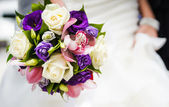 Wedding bouquet with different flowers in hands of bride — Stock Photo