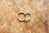 Two gold wedding rings on wooden vintage backgrounds — Stock Photo