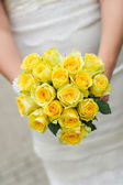 Wedding bouquet with many yellow roses in hands of bride — Stock Photo