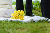 Roses bouquet  lying in grass on wedding ceremony — Stock Photo