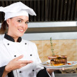 Young beautiful female chef presenting food — Stock Photo #10674544