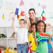 Preschool kids and teacher with flags in classroom — Stock fotografie #10683323