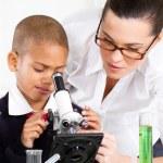Beautiful young teacher helping school boy — Stock Photo #10983543