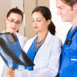 Group of medical workers in hospital looking at x-ray - Stock Photo
