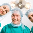 Happy doctors looking at patient after successful surgery - Stock Photo