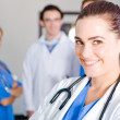 Pretty young female doctor and colleagues — Stock Photo #12037342