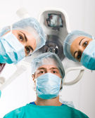 Group of surgeons looking at patient in operation room — Stock Photo