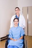 Nurse pushing patient on wheel chair in hospital — Stock Photo