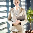 Pretty young businesswoman standing by office window — Stock Photo