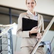 Beautiful young businesswoman standing by stairs — Stock Photo