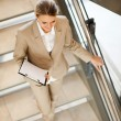 Attractive young businesswoman walking down stairs — Stock Photo