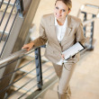 Gorgeous young businesswoman walking up stairs — Stock Photo