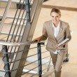 Stock Photo: Cute young businesswoman walking up stairs