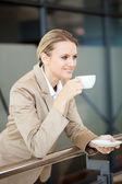 Young beautiful businesswoman drinking coffee — Stock Photo