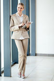 Happy young businesswoman full length portrait with a tablet computer — Stock Photo