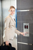 Beautiful young businesswoman using elevator — Stock Photo