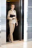 Bella giovane imprenditrice uscendo ascensore — Foto Stock