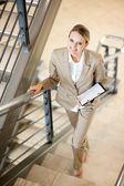 Hermosa joven empresaria subiendo escaleras — Foto de Stock