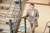 Cute young businesswoman walking up stairs — Stock Photo