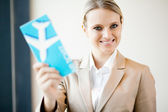 Attractive young businesswoman holding air ticket — Stock Photo