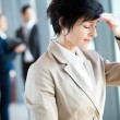 Middle aged businesswoman having headache in office - 图库照片