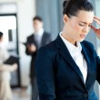Young businesswoman having headache at work — Stock Photo