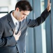 Young businessman having heart attack or chest pain - Foto Stock