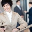 Middle aged businesswoman using smart phone — Stock fotografie