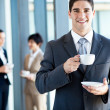 Young businessman having coffee break in office — Foto de Stock