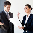 Two young colleagues arguing over paperwork in office — Stock Photo #12288247