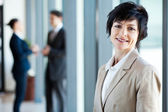 Middle aged businesswoman in office with colleagues — Stock Photo